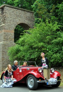 """Petticoats und Oldtimer vor römischer Kulisse: Das Aquädukt in Vussem bildete den Hintergrund fürs Erinnerungsfoto mit den """"Motor-Girls"""". Foto: Renate Hotse/pp/Agentur ProfiPress"""