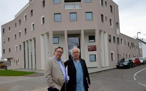 Rolf K. Emmerich (l.) und Rolf A. Kluenter posieren vor dem City-Süd-Gebäude, das von der Euskirchener gemeinnützigen Baugesellschaft (Eugebau) errichtet wurde. Foto: Manfred Lang/pp/Agentur ProfiPress