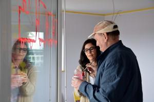 Die Therapeutin Ute Keils spiegelt sich in dem Werk, das der autistische Künstler Stephan Albach aus Zülpich auf Glas gemalt hat. Foto: Manfred Lang/pp/Agentur ProfiPress