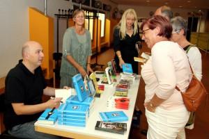 Nach der Lesung mit anschließender Fragerunde signierte Frank Goosen am Büchertisch der Buchhandlung Lesezeichen aus Hillesheim noch Exemplare seiner Romane. Auch der ein oder andere Plausch mit Besuchern war drin. Foto: Thomas Schmitz/pp/Agentur ProfiPress