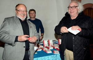 """Die beiden Lit.Eifel-Vertreter Manfred Lang (l.) und Helmut Lanio erstanden am Büchertisch der Kaller Buchhandlung Pawlik ein Exemplar von Luna Al-Mouslis Buch """"Eine Träne. Ein Lächeln"""", um es sich anschließend von der Autorin signieren zu lassen. Foto: Sarah Winter/pp/Agentur ProfiPress"""