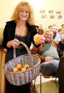 """Passend zur zuvor gehörten Sage verteilte Katia Franke Äpfel an die Zuhörer der Klosterkapelle. Sie sollen """"ewige Jugend"""" verleihen. Foto: Kirsten Röder/pp/Agentur ProfiPress"""
